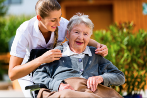 A senior smiling with her caregiver